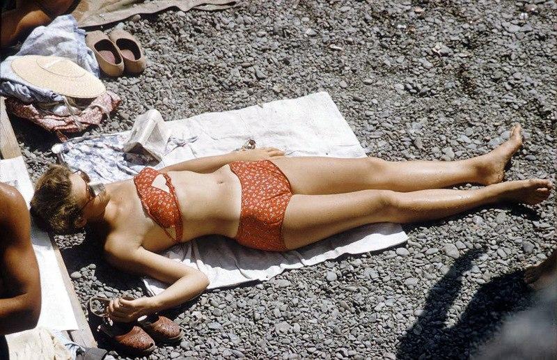Отдыхающие на пляже греются на солнышке