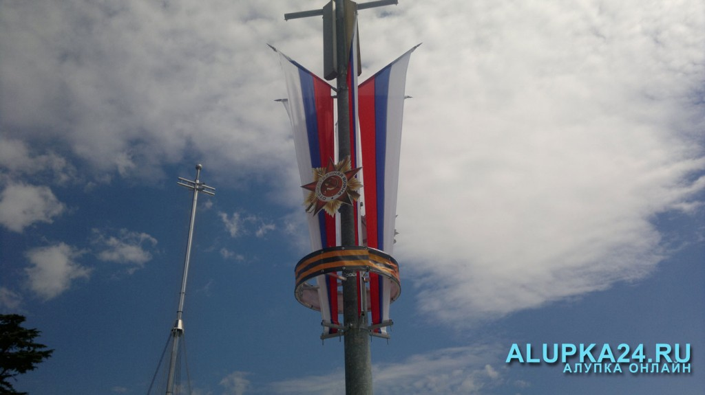 Столбы украшают георгиевской лентой и значком Победы