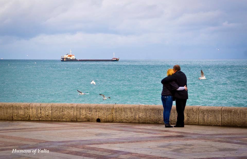 Пара на набережной, любующаяся морем