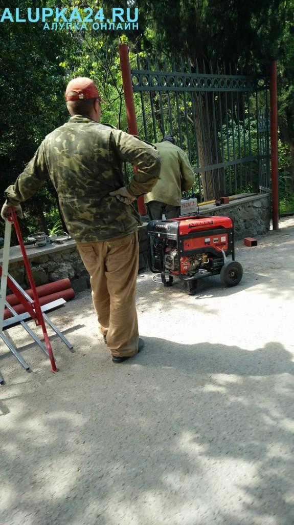 Рабочие устанавливают забор вокруг Воронцовского парка